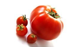 Un tomates grandes y tres pequeños. Fotos de archivo libres de regalías