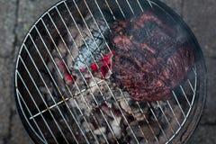 Un top abajo de la visión de una falda de carne de vaca grande y barbequed en una pequeña parrilla del hibachi del carbón de leña imagen de archivo