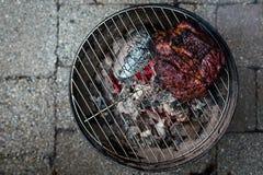 Un top abajo de la visión de una falda de carne de vaca grande y barbequed en una pequeña parrilla del hibachi del carbón de leña imagenes de archivo