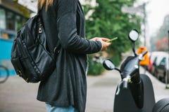 Un touriste avec un sac à dos va utiliser un scooter électrique par une application mobile dans le téléphone et d'une manière dis Photographie stock libre de droits