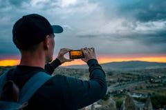 Un touriste d'une taille regardant le coucher du soleil au-dessus de la ville de Goreme en Turquie fait une photo Cappadocia Tour Photo libre de droits