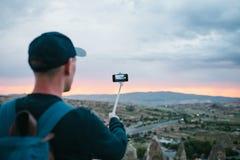 Un touriste d'une taille regardant le coucher du soleil au-dessus de la ville de Goreme en Turquie fait une photo Cappadocia Tour Images libres de droits