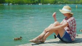 Un touriste de femme appréciant des vacances au lac où les canards nagent Ressource en Espagne clips vidéos