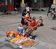 Un touriste et des personnes âgées parlent des marchandises vendant des arts et des métiers Photos libres de droits