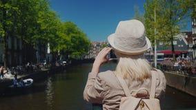 Un touriste féminin dans un chapeau et avec un sac à dos décrit une belle vue du canal à Amsterdam Tourisme dans clips vidéos