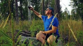 Un touriste masculin dans les lunettes de soleil et une casquette de baseball dans la forêt s'assied sur un arbre tombé et prend  clips vidéos