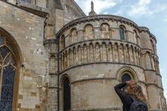 Un touriste observe soigneusement la façade d'une partie de la cathédrale catholique de style médiéval dans la ville de Norwich images libres de droits