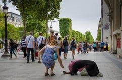 Un touriste place des pièces de monnaie dans la tasse d'une femme priant sur le trottoir de Champs-Elysees Images libres de droits