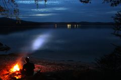 Un touriste s'assied par un feu de camp la nuit photo libre de droits