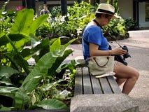 Un touriste se repose sur un banc de parc et regarde des photos Photo stock