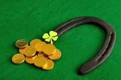 Un trébol, un zapato del caballo y monedas de oro Fotografía de archivo
