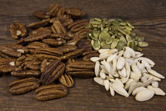 Un trío de las nueces estupendas crudas de la comida, incluyendo las pacanas, la calabaza cruda y las semillas de calabaza Imágenes de archivo libres de regalías