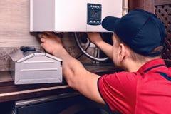 Un trabajado cualificado joven regula la caldera de gas antes de usar imagen de archivo