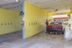 Un trabajador aclara un coche negro en el túnel de lavado foto de archivo libre de regalías