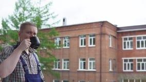 Un trabajador bebe una bebida caliente de una taza negra contra un edificio de ladrillo almacen de metraje de vídeo