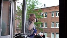 Un trabajador bebe una bebida caliente de una taza negra contra un edificio de ladrillo metrajes