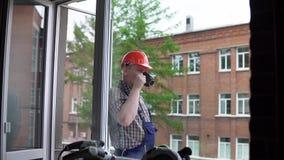 Un trabajador bebe una bebida caliente de una taza negra contra un edificio de ladrillo almacen de video