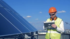 Un trabajador comprueba los paneles en un tejado Un ingeniero examina calidad del ` de los paneles del sol metrajes