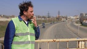 Un trabajador con una barba y un bigote est? en el puente que fuma un cigarrillo y que quita un casco amarillo de su cabeza v?deo almacen de video