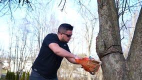 Un trabajador corta peligroso en un árbol con la motosierra en el parque local almacen de metraje de vídeo