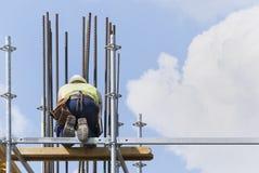 Un trabajador de construcción en una alta pared Fotos de archivo