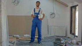 Un trabajador de construcción joven habla con la cámara - una casa bajo construcción en el fondo metrajes