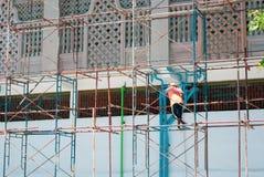 Un trabajador de construcción que se coloca en el andamio de acero que comprueba w azul fotografía de archivo