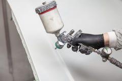 Un trabajador de sexo masculino pinta con un arma de espray a la parte de la carrocería en plata después de ser dañado en un acci fotografía de archivo