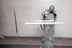 Un trabajador de sexo masculino pinta con un arma de espray a la parte de la carrocería en plata después de ser dañado en un acci imagen de archivo libre de regalías