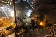 Un trabajador del carbón de leña en el trabajo sobre una pila de charcoa de madera ardiente lento Imagen de archivo libre de regalías
