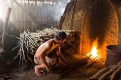 Un trabajador del carbón de leña en el trabajo sobre una pila de charcoa de madera ardiente lento Imagen de archivo