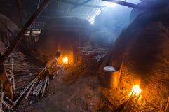 Un trabajador del carbón de leña en el trabajo sobre una pila de charcoa de madera ardiente lento Fotos de archivo libres de regalías