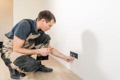Un trabajador del electricista en el trabajo de la instalación del zócalo del cable de cableado y del interruptor de la luz o del fotografía de archivo