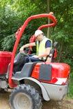 un trabajador del hombre del emplazamiento de la obra que conduce el cavador Fotografía de archivo