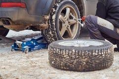 Un trabajador del servicio del neumático que substituye las ruedas fotografía de archivo libre de regalías