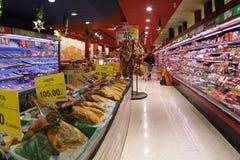 Un trabajador del supermercado que llena la acción en los refrigeradores Fotos de archivo libres de regalías