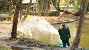 Un trabajador en céspedes de riego de un parque con una bomba de un lago metrajes