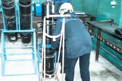 Un trabajador en un casco está cargando un cilindro de oxígeno del gas sobre una carretilla en una planta industrial imagen de archivo libre de regalías