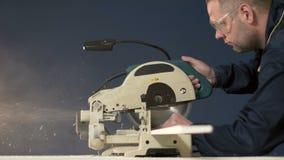 Un trabajador en un fondo azul baja la sierra y controla el árbol 4K almacen de metraje de vídeo