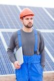 Un trabajador en la estación de la batería solar, vestida en un uniforme, guarda una tableta y mira en alguna parte Fotos de archivo libres de regalías