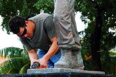 Un trabajador en Miami repara la estatua de Nestor Antonio Izquiero Fotografía de archivo