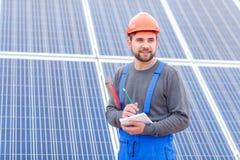 Un trabajador en una estación de la energía solar en uniforme mira en alguna parte y escribe en un cuaderno que sostiene waterpas Fotos de archivo libres de regalías