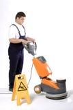 Un trabajador es suelo de la limpieza con la limpieza Foto de archivo