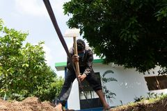 Un trabajador está cavando un agujero usando la azada en el jardín imagen de archivo libre de regalías