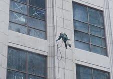 Un trabajador está lavando el edificio situado en Shangai Imágenes de archivo libres de regalías