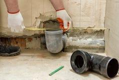 Un trabajador está midiendo el tubo de desagüe de las aguas residuales imagen de archivo libre de regalías