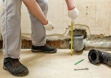 Un trabajador est? midiendo el tubo de desag?e de las aguas residuales fotos de archivo libres de regalías