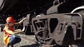 Un trabajador ferroviario de la mujer joven comprueba la unidad del tirón del carro de la carga almacen de metraje de vídeo