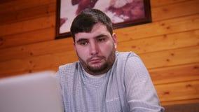 Un trabajador independiente del hombre en cuestión que se sienta por el ordenador portátil almacen de metraje de vídeo