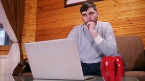 Un trabajador independiente desconcertado del hombre que se sienta por el ordenador portátil almacen de video